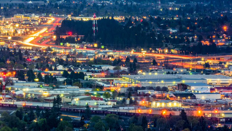Valley view of trains, freeway at night